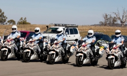 Graduates from the Advanced Motorcycle Program line up in formation on their motorcycles.