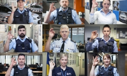 "Image of nine police officers making an ""OK"" hand signal"