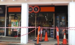 Image of damaged Charnwood BWS Liquor shop front which has been taped off.
