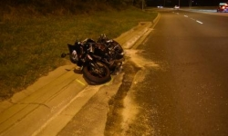 Motorbike crashed on the kerb of the road with debris