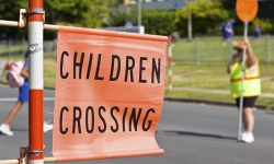 Sign saying childrens crossing erected outside a school where children are crossing a road